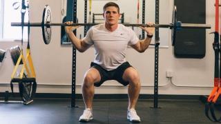Esecuzione di squat con bilanciere