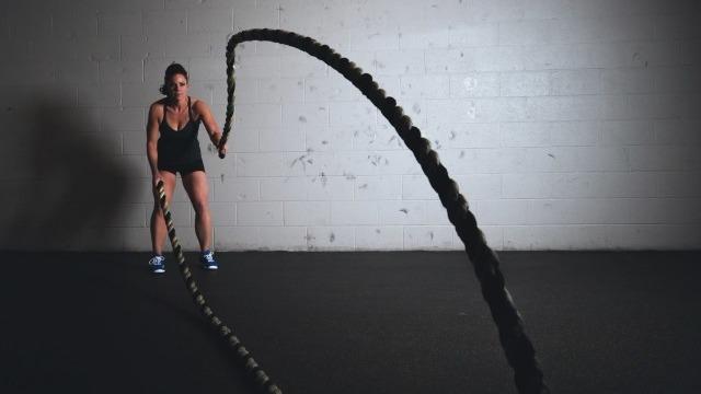 Ragazza che si esercita con le battle ropes