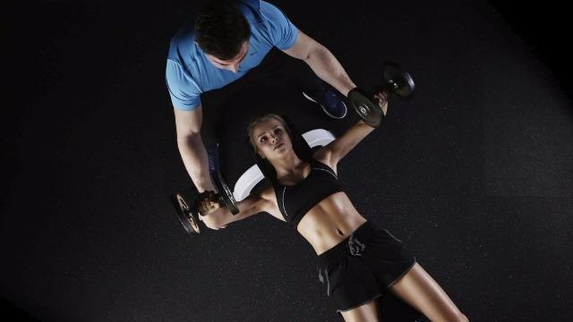 Personal trainer assiste cliente durante esercizio di distensioni con manubri su panca piana