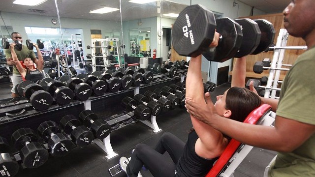 Esecuzione di Shoulder Press con manubri da seduti con spotter in assistenza