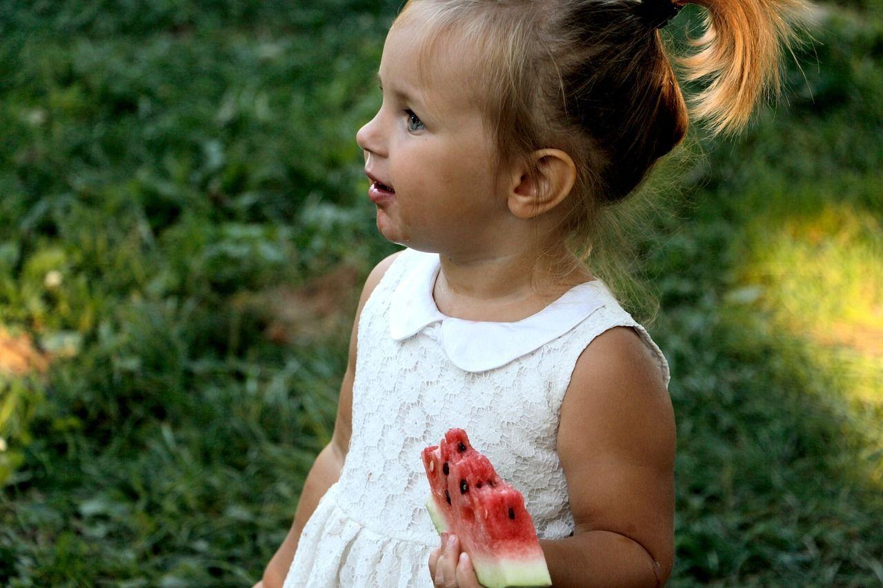 Una bambina con una fetta di anguria