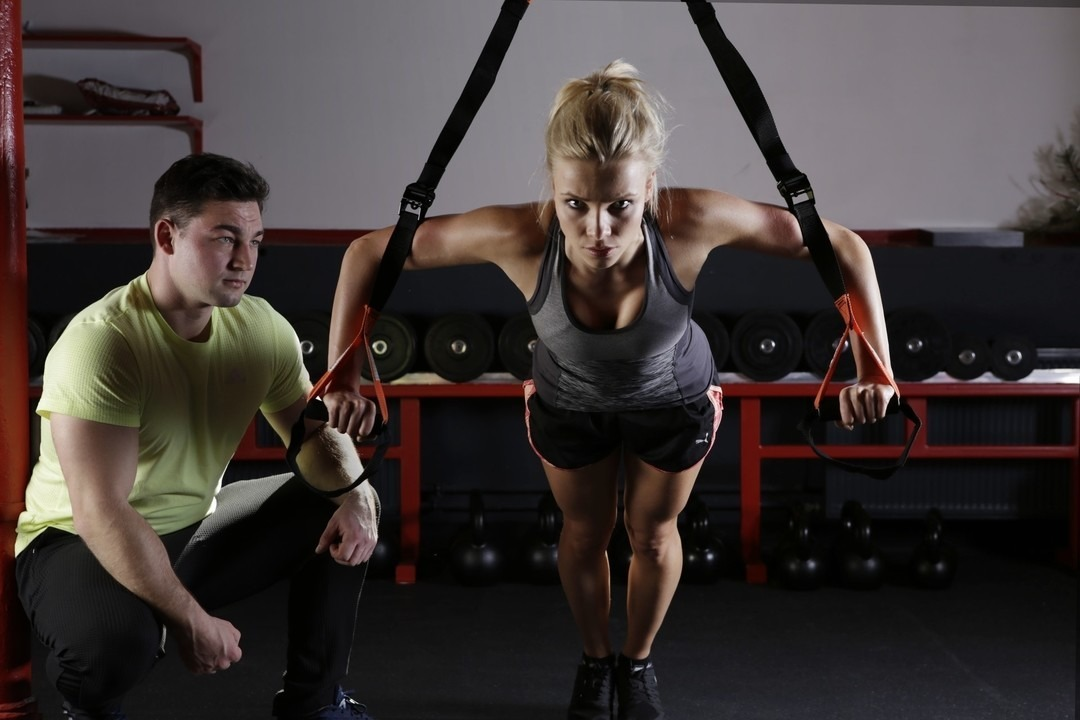 Personal trainer e cliente durante esercizio con TRX